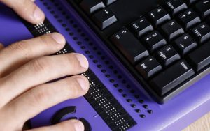Photo: Blind person using computer with braille computer display